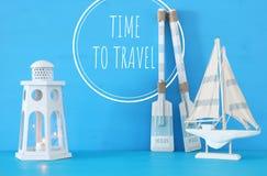 Seekonzept mit weißer dekorativer Leuchtturmlaterne, hölzernen Rudern und Boot über blauem Hintergrund stockbilder