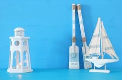 Seekonzept mit weißer dekorativer Leuchtturmlaterne, hölzernen Rudern und Boot über blauem Hintergrund stockfotos