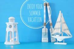 Seekonzept mit weißer dekorativer Leuchtturmlaterne, hölzernen Rudern und Boot über blauem Hintergrund stockfoto