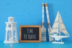 Seekonzept mit weißer dekorativer Leuchtturmlaterne, hölzernen Rudern und Boot nahe bei Tafel über blauem Hintergrund lizenzfreie stockfotos