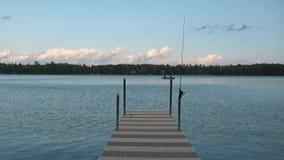 Seelandschaft mit Dock, Angelrute und Fischerboot stock footage