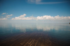 Seelandschaft mit Wolkenreflexionen Lizenzfreie Stockfotos