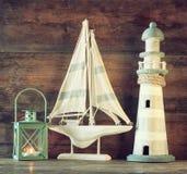 Seelebensstilabendkonzept alter Weinleseleuchtturm, -Segelboot und -laterne auf Holztisch Weinlese gefiltertes Bild Lizenzfreies Stockfoto