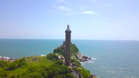 Seeleuchtturm auf Felseninsel in der Luftlandschaft des blauen Wassers Brummenansicht-Leuchtturmturm auf grüner Insel im Ozean stock video
