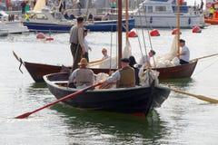 Seeleute in der Weinlese kleidet das Rudern von alten Segelschiffen im harbo lizenzfreie stockfotografie