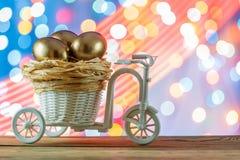 Seemöwe, die auf einem Flussrand steht Goldene Eier in einem Fahrradwarenkorb ei Fröhliche Ostern Lizenzfreie Stockfotos