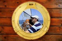 Seemann auf Segelboot, vom Bootsfenster Lizenzfreie Stockfotos