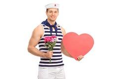 Seemann, der Blumen und ein Herz hält Stockfotografie