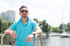 Seemann in der schwarzen Sonnenbrille auf Schiffsbrett Hübscher goateed Mann auf dem Boot, das zu weit schaut Reisetourismusferie stockfotografie