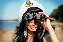 Seemannfrau mit Ferngläsern macht einen Spaziergang auf der Seeküste Stockfoto