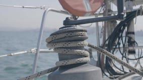 Seemannmann, der Segelhandkurbel und -seil beim auf Yacht oben segeln im Seeabschluß verwendet stock video