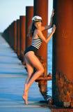 Seemannmodell in der stilvollen Badeanzug- und Kapitänhutaufstellung sexy auf dem hölzernen Pier Stockbild