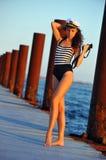 Seemannmodell im stilvollen Badeanzug, der Ferngläser und Stellung auf dem hölzernen Pier hält Lizenzfreie Stockfotos