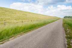 Seemingly endless road along an embankment and a fence Stock Images