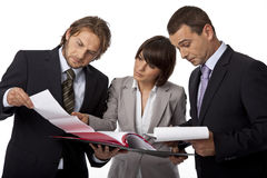Seems like trouble. Three serious businesspeople isolated on white making analysis Stock Image