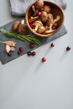 Seen from above, fall fruits and mushrooms. Cranberries are scattered across a slate board, lying next to garlic, and rosemary. Seen from above, a wooden bowl stock image