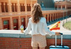 Traveller woman with trolley bag, Spain flag and green smoothie. Seen from behind elegant traveller woman with trolley bag, Spain flag and green smoothie near stock photos