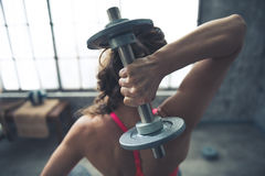 Seen from behind fitness woman lifting dumbbell Royalty Free Stock Images