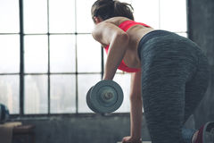 Seen from behind fitness woman lifting dumbbell in loft gym Stock Photo