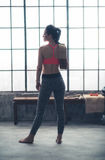 Seen from behind fitness woman with towel standing in loft gym Royalty Free Stock Image