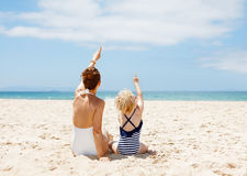 Seen from behind mother and child pointing up at sandy beach Royalty Free Stock Photos