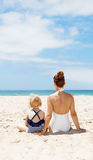 Seen from behind mother and child in swimsuits sitting at beach Royalty Free Stock Photos
