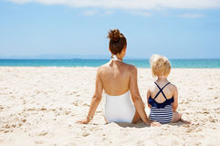 Seen from behind mother and child in swimsuits sitting at beach Stock Photos