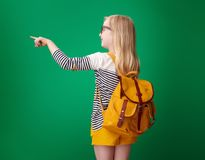School girl pointing at something on green background. Seen from behind school girl with backpack pointing at something on green background stock image