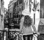 Seen from behind tourist woman in Venice having excursion. Venice. Off the Beaten Path. Seen from behind elegant tourist woman in fur hat in Venice, Italy in the Royalty Free Stock Images