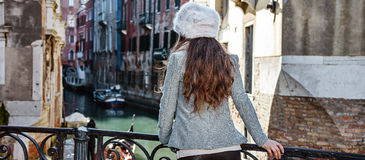 Seen from behind tourist woman in Venice, Italy having excursion. Venice. Off the Beaten Path. Seen from behind elegant tourist woman in fur hat in Venice, Italy stock images