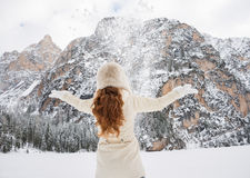 Seen from behind woman in coat and hat throwing snow outdoors Stock Photos