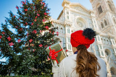 Seen from behind, woman holding Christmas gift box in Florence Stock Photo