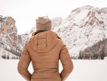 Seen from behind woman outdoors looking on snow-capped mountains Royalty Free Stock Photography