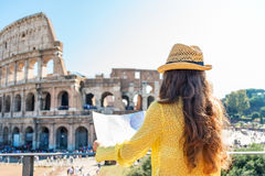 Seen from behind, a woman tourist holding a map at Colosseum. On hot summers day, a woman is seen from behind and is holding a map of Rome. She is looking out Stock Photo