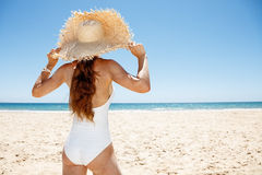 Seen from behind woman in white swimsuit and straw hat at beach Royalty Free Stock Image