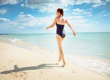 Seen from behind young woman in swimwear on seacoast walking stock image