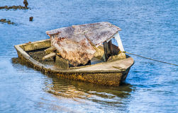 Seen Better Days Boat. A decaying wreck of a boat covered with barnacles rests in the harbor near Beaufort, North Carolina Royalty Free Stock Photography