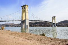 Seen cable-stayed bridge in sunny winter afternoon from unpaved Stock Photos