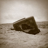 Seen enough?. Retro/vintage sepia image of a broken television on the beach Royalty Free Stock Images
