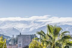 Alhambra with palm tree and white Nevada mountains royalty free stock photos