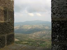 Seen by the window of a fortitude of the hills of the Tuscan in Valley of Orcia. Radicofani. Italy royalty free stock photo