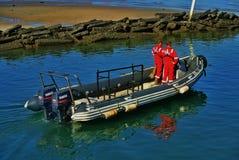 Seenotrettungsmänner auf einem Gummi schmuddelig stockbilder