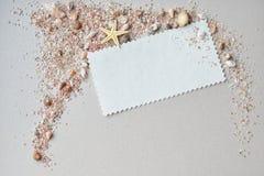 Seeoberteile, rosa Sand und Einladungskarte auf einem Papierhintergrund Lizenzfreie Stockbilder