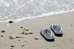 Seeoberteile und Flipflops auf Sand Volleyballkugel auf leerem schönem Strand oberseite Stockfoto