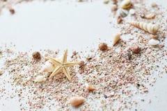 Seeoberteile und rosa Sand mit einem Starfish auf einem weißen Hintergrund Lizenzfreie Stockfotografie