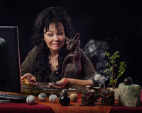 Seer uses gemstones for online future prediction. Portrait of female fortuneteller works on-line with semi-precocious gemstones. The mature black haired diviner Stock Photo
