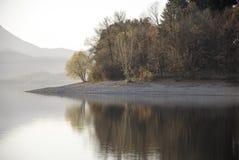 Seereflexion mit Herbstbäumen und klarem Himmel Stockfoto