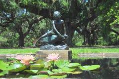 Seerosen in einem Pool mit dem Anstarren der Statue Stockfotos