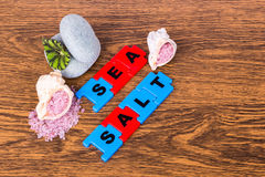 Seesalz, Beschriftung, Blattanlagen und zwei Steine, die auf Holz liegen lizenzfreie stockfotografie