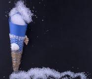 Seesalz in einer blauen Papiertüte wird auf einen schwarzen Hintergrund zerstreut Stockfotos